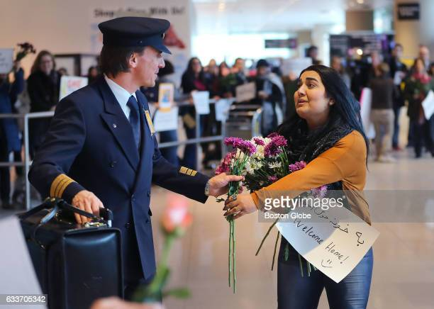 A volunteer hands a flower to a flight crew member of Lufthansa Air the flight where many whom had been denied entry flew on and arrived at Logan...