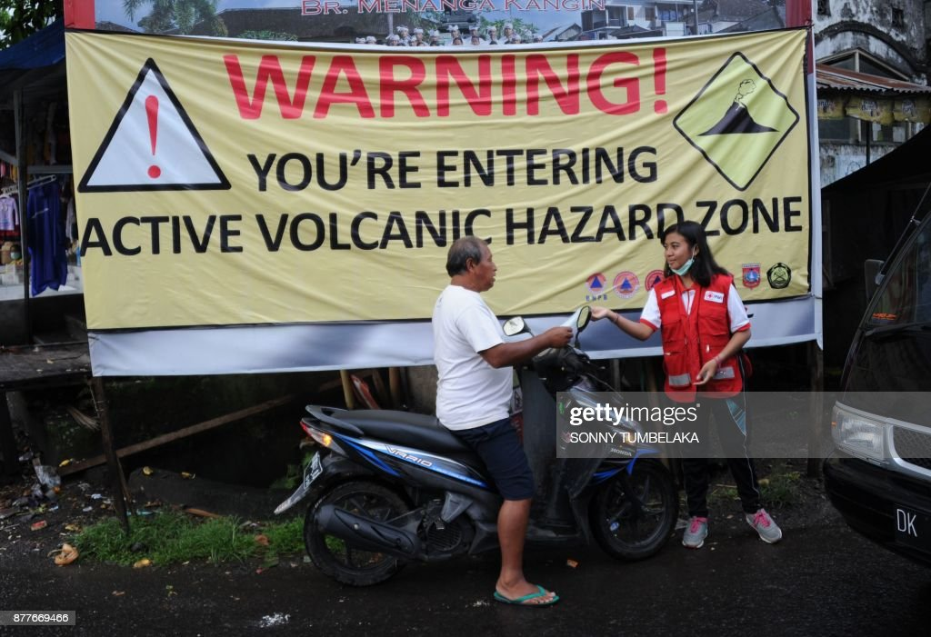 A volunteer hands out a mask to a motorist due to ash in the air from Mt. Agung volcano, at a traditional market in the Rendang sub-district of Karangasem Regency on Indonesia's resort island of Bali on November 23, 2017. Thousands living in the shadow of the rumbling volcano on Indonesia's resort island of Bali fled on November 22 as fears grow that it could erupt for the first time in more than 50 years. /