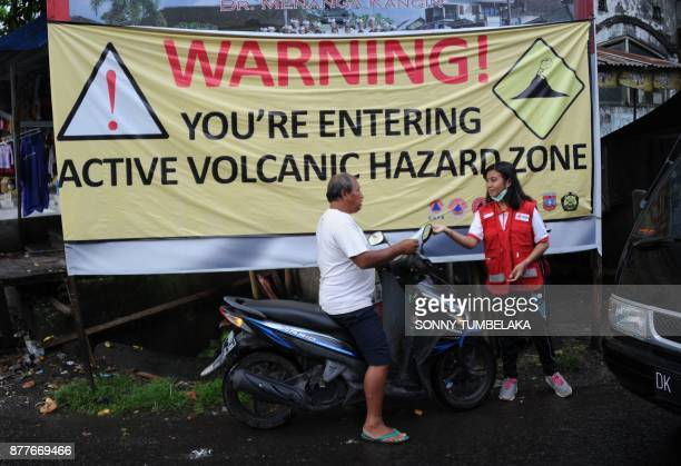 A volunteer hands out a mask to a motorist due to ash in the air from Mt Agung volcano at a traditional market in the Rendang subdistrict of...