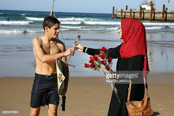 A volunteer hands out a rose to a surfer as part of the Petals for Palestine Peace Project to members of the public at the North Beach in Durban on...