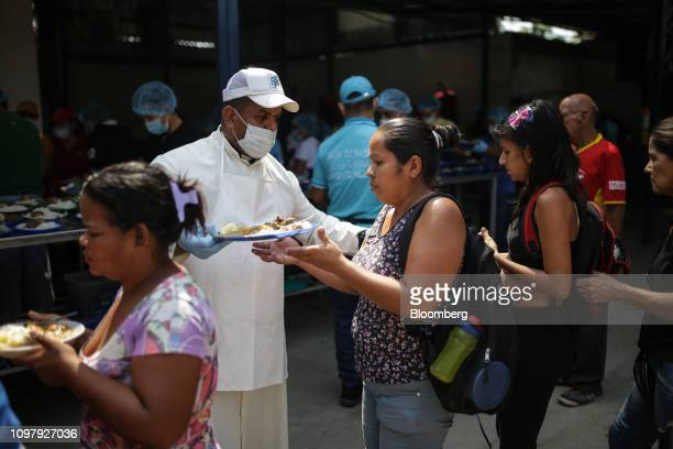 A volunteer hands out food at the Casa de Paso La Divina Providencia soup kitchen during a meal service for Venezuelan migrants in the town of La...
