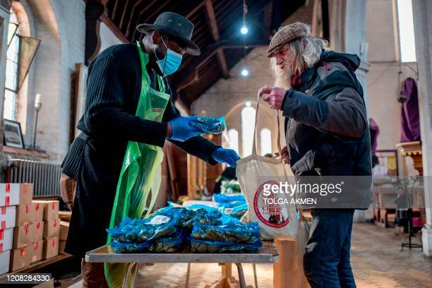 A volunteer hands out food to peopleinneed at a popup shop serving as food bank at St Margaret's Church in Leytonstone amidst the novel coronavirus...