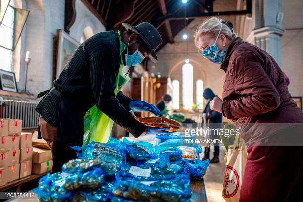 Volunteer hands out food to people-in-need at a pop-up shop serving as food bank at St Margaret's Church in Leytonstone, amidst the novel coronavirus...
