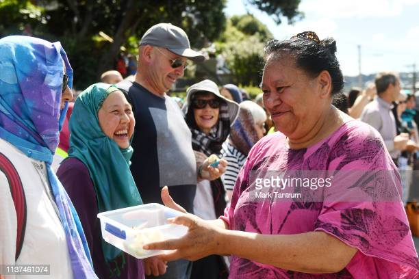 A volunteer hands out refreshments to members of the public gathered as part of the Human Chain of Protection and Solidarity outside the Mosque in...