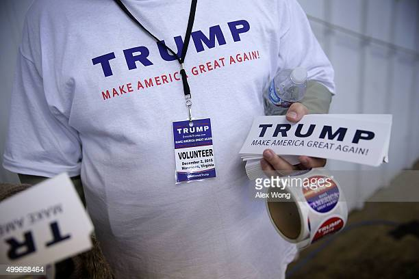 A volunteer hands out stickers prior to a campaign rally of Republican presidential candidate Donald Trump December 2 2015 in Manassas Virginia Trump...