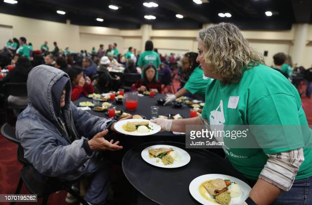 A volunteer hands out Thanksgiving meals to guests during the 27th Annual Thanksgiving Dinner for the community on November 20 2018 in Oakland...