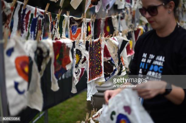 A volunteer hangs traditional Aboriginal art painted by school children up to dry at Sydney's Hyde Park on July 3 2017 The week long annual event...