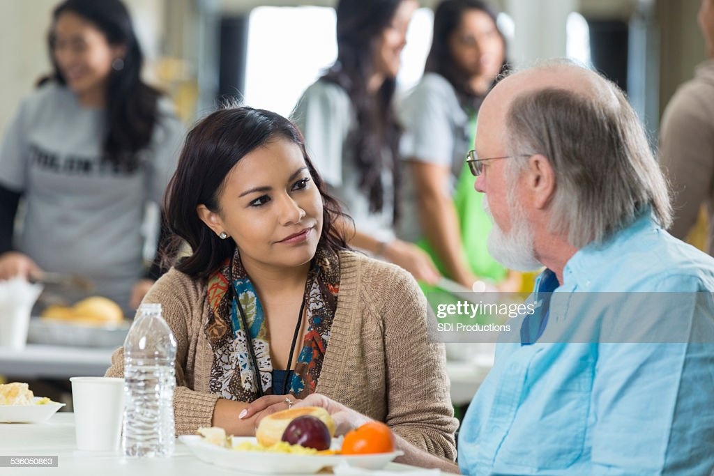 Volunteer having meal with senior man at soup kitchen : Stock Photo