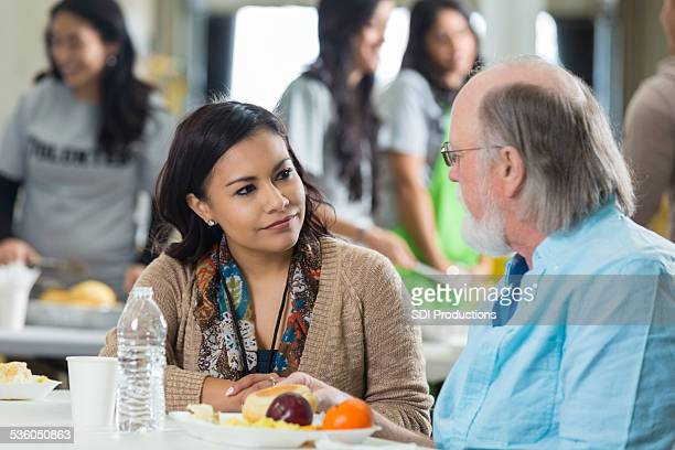 volunteer having meal with senior man at soup kitchen - depression bread line stock pictures, royalty-free photos & images