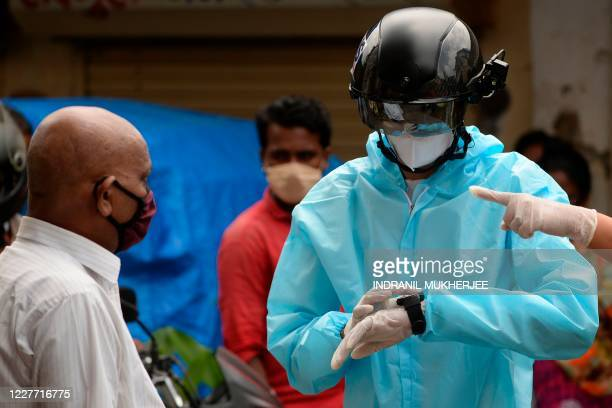 A volunteer health worker of the NonGovernmental Organization Bharatiya Jain Sanghatana wearing Personal Protective Equipment using a smart helmet...