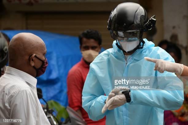 Volunteer health worker of the Non-Governmental Organization Bharatiya Jain Sanghatana wearing Personal Protective Equipment using a smart helmet...