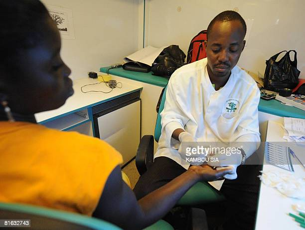 A volunteer health worker retrieves blood sample for an HIVAIDS detection test on a patient on June 18 2008 in Noe a city in Ivory Coast close to the...