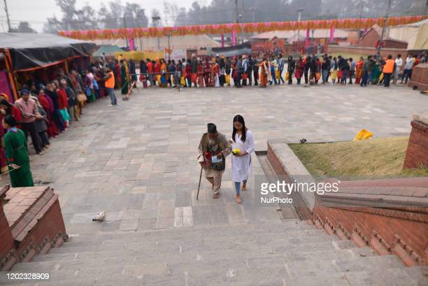 A volunteer help an old man to worship in the temple during Maha Shivaratri at the premises of Pashupatinath Temple Kathmandu Nepal on Friday...