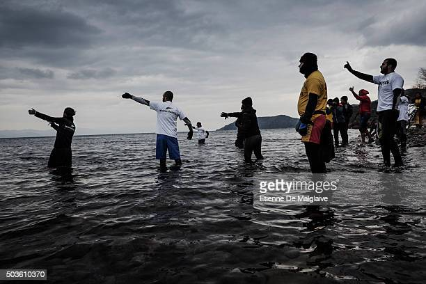 Volunteer helpers signal where to run ashore to an incoming rubber boat crowed with refugees on January 3 2016 near Skala Sikaminias Greece Lesbos...