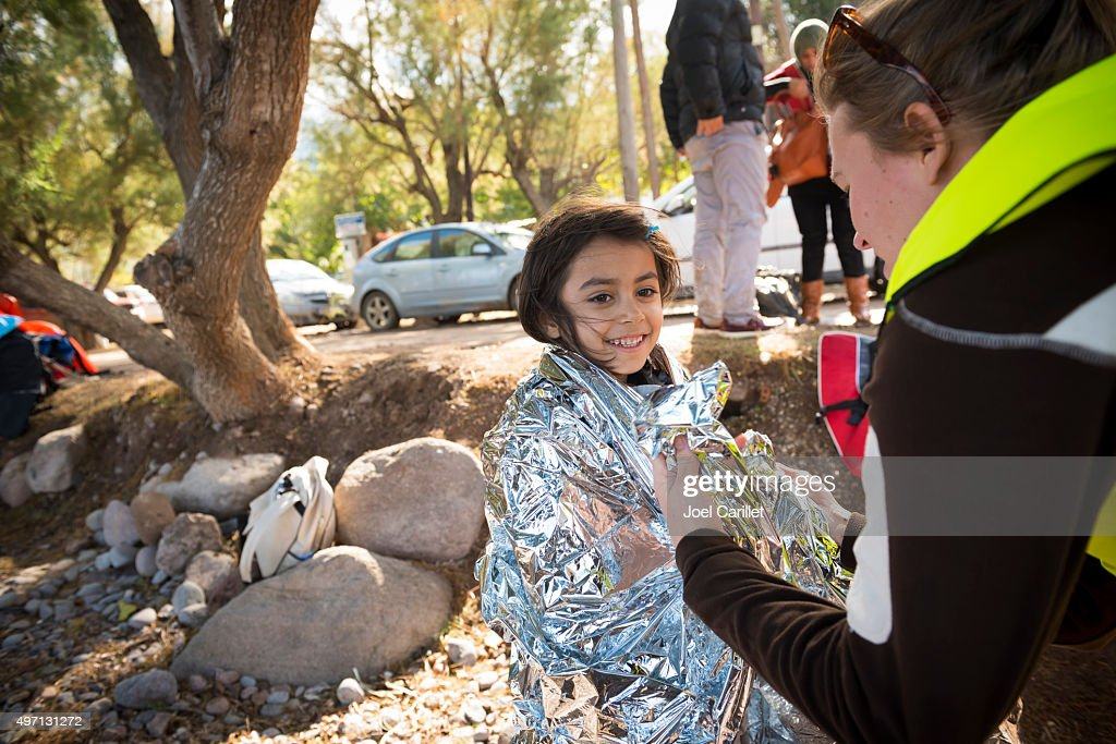 Volunteer helping refugee girl on beach : Stock Photo