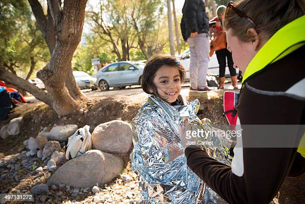 volunteer helping refugee girl on beach - ongelukken en rampen stockfoto's en -beelden