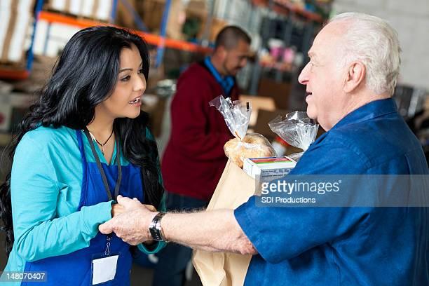 Volunteer helping senior man with groceries at a food bank