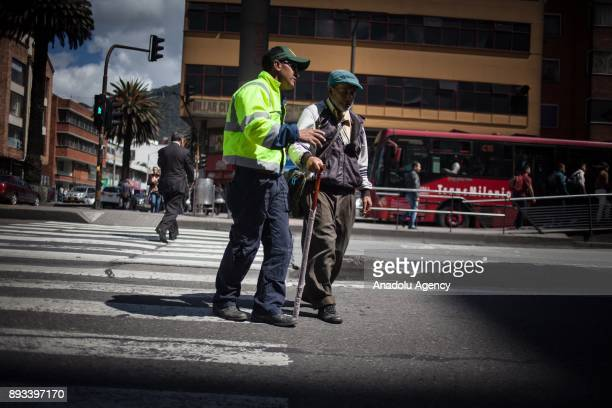 A volunteer helps a homeless man with crossing the road in Bogota Colombia on December 15 2017 Homeless people who are called 'CHC' Ciudadanos...