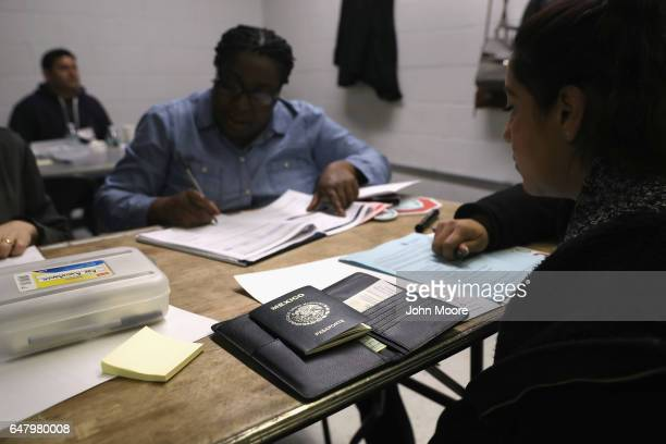 A volunteer helps a Mexican immigrant to complete her US citizenship application at a CUNY Citizenship Now event held in the Bronx on March 4 2017 in...