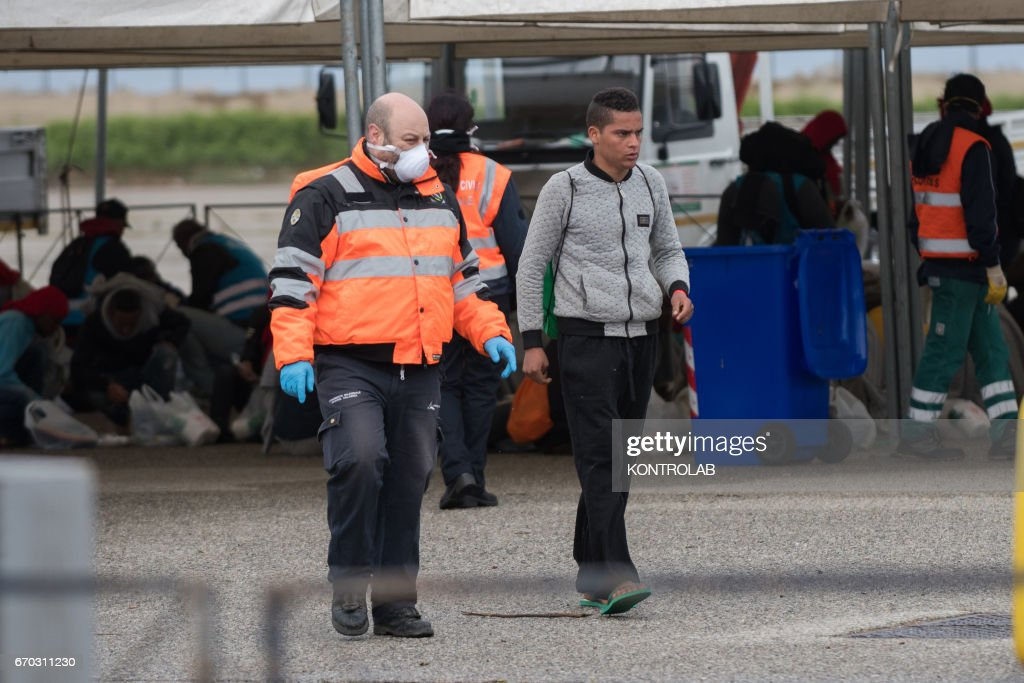 A volunteer helps a migrant unaccompanied minor during the