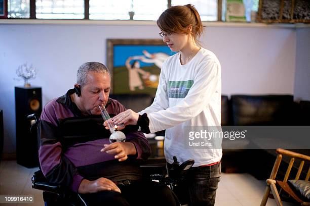 A volunteer helps Alex Barak to smoke cannabis at the Tikun Olam company clinic on March 03 2011 in Tel Aviv Israel In conjunction with Israel's...