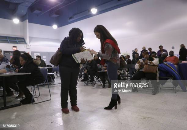 A volunteer helps an immigrant to complete her US citizenship application at a CUNY Citizenship Now event held in the Bronx on March 4 2017 in New...
