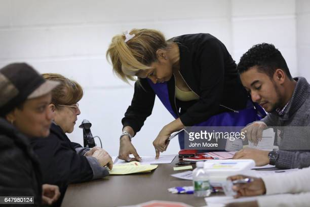 Volunteer helps immigrants to complete their U.S. Citizenship applications at a CUNY Citizenship Now! event held in the Bronx on March 4, 2017 in New...