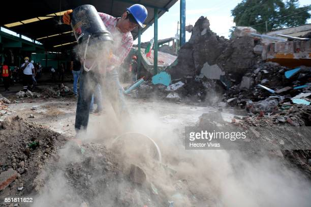 A volunteer helps remove the debris from a collapsed building three days after the magnitude 71 earthquake jolted central Mexico killing more than...