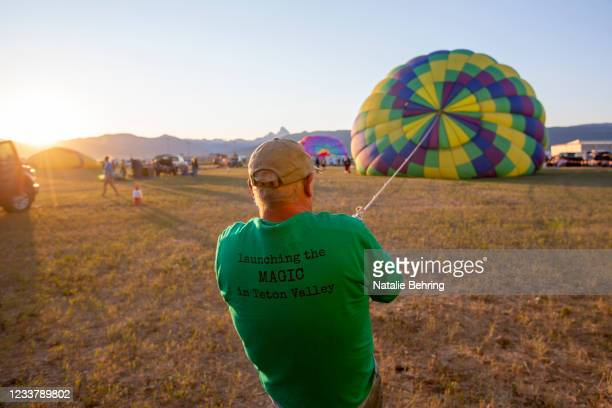 Volunteer helps to inflate a hot air balloon at the Teton Valley Balloon Rally on July 3, 2021 in Driggs, Idaho. The rally has been an annual event...