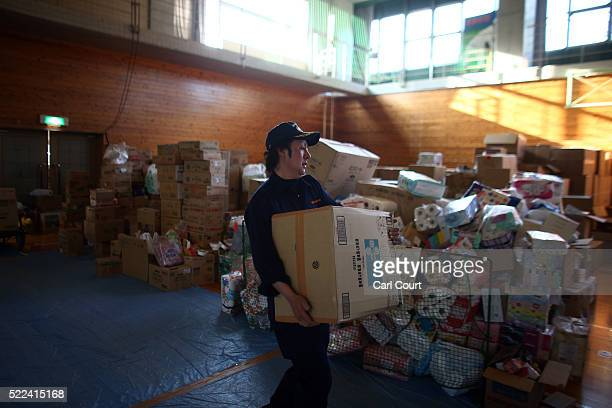 A volunteer helps with boxes of donations and relief supplies at a distribution centre following an earthquake on April 19 2016 in Minamiaso near...