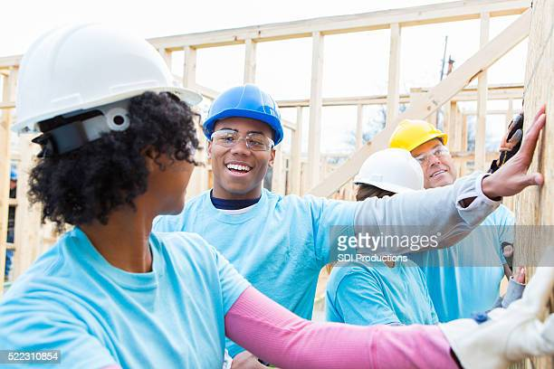 Volunteer hold up wall at construction site