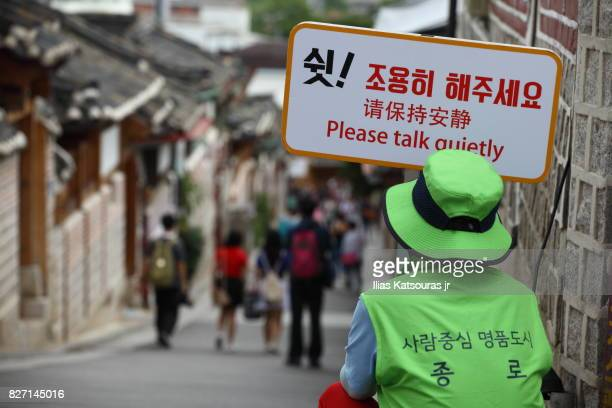 Volunteer holding sign in busy touristic neighborhood