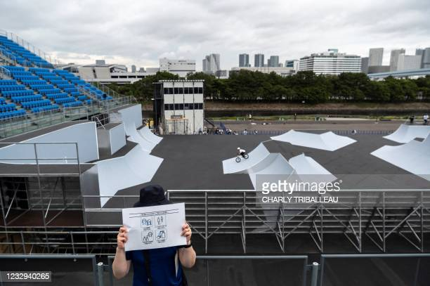 Volunteer holds a placard showing Covid-19 coronavirus prevention measures at the BMX freestyle track venue during a test event for the Tokyo 2020...