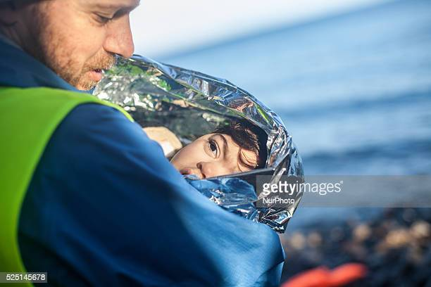 A volunteer holds a refugee child / Skala Skamnias January 13 2016 Last summer up to 120 boats arrived each day on the northeastern coast of the...