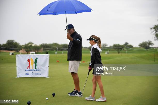 Volunteer holds an umbrella for a competitor during the 2021 Drive, Chip and Putt Regional Qualifier at TPC Scottsdale on September 26, 2021 in...