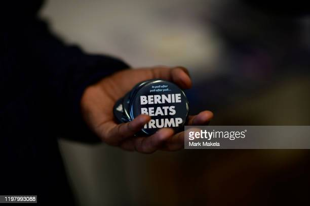 Volunteer holds campaign buttons at a field office before canvassing for Democratic Presidential candidate Bernie Sanders on February 1, 2020 in...