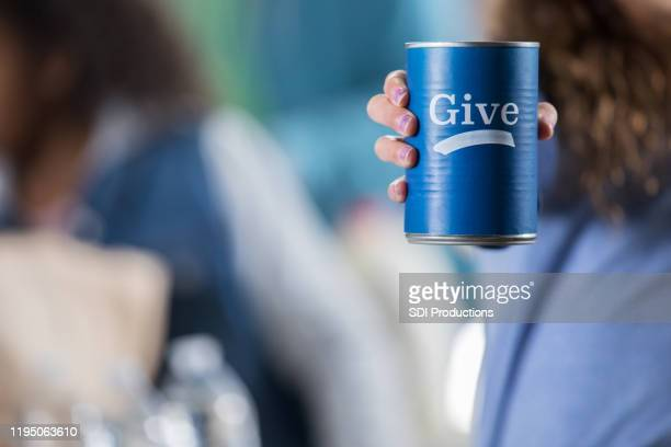 volunteer holds donation can during food drive - food drive stock pictures, royalty-free photos & images
