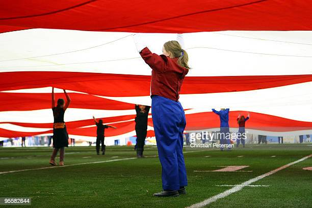 A volunteer holds up the flag during the national anthem before the Tostitos Fiesta Bowl between the Boise State Broncos and the TCU Horned Frogs at...