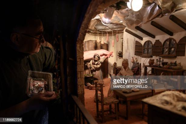 Volunteer Ilario Geuna cleans a nativity figure at the 43rd edition of the Presepio of Cavallermaggiore a 300sqm Christmas Nativity crib in the...