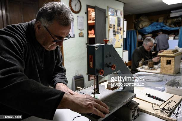 Volunteer Ilario Geuna uses a sewing machine as he builds a small house for the Presepio of Cavallermaggiore a 300sqm Christmas Nativity crib in the...