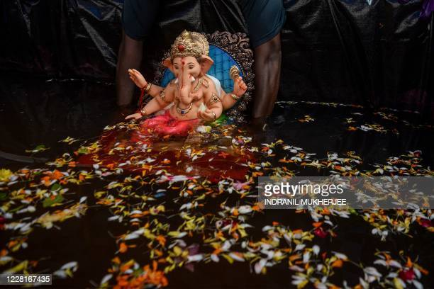 TOPSHOT A volunteer immerses a clay idol of Hindu elephantheaded deity Ganesh in an artificial tank in Mumbai on August 23 2020 India's muchloved...