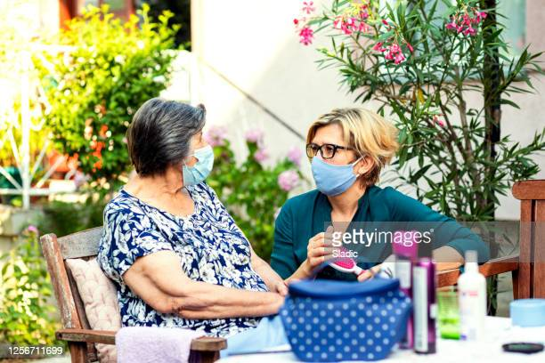 volunteer in home visit at senior woman,cares about hers hygiene - nursing assistant stock pictures, royalty-free photos & images