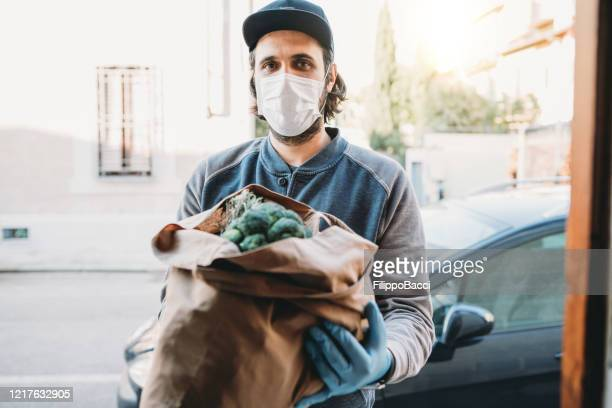 a volunteer is delivering a bag of vegetables and fruit - epidemic stock pictures, royalty-free photos & images