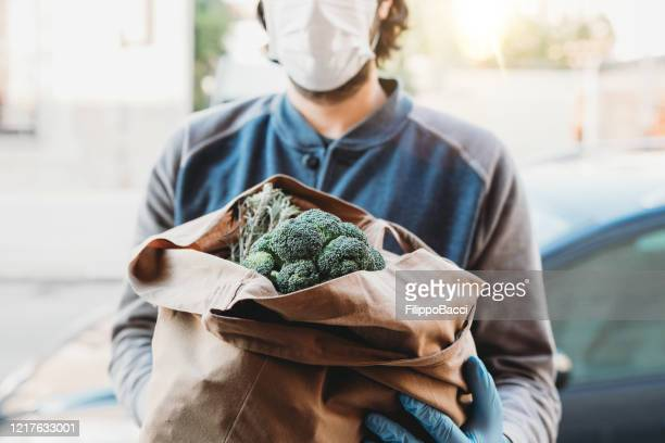 a volunteer is delivering a bag of vegetables and fruit - stay at home order stock pictures, royalty-free photos & images