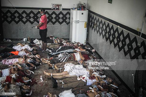 Volunteer is seen in a makeshift morgue filled with dead bodies of supporters of ousted president Mohammed Morsi after clashes between the security...
