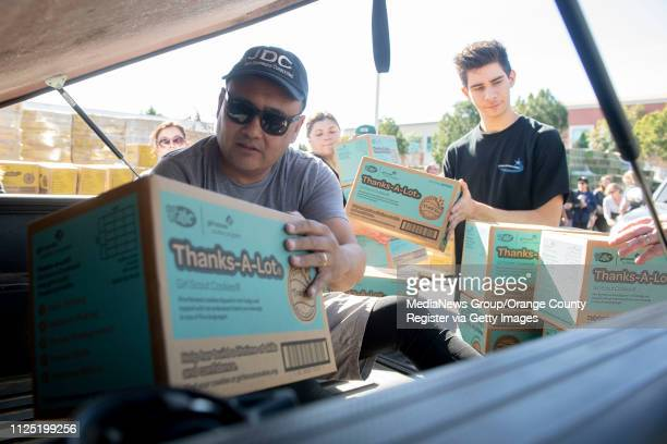 Volunteer Jeff Dronkers of Cypress climbs into the bed of a pickup truck as he helps load ThanksALots during the Girl Scout Cookie Mega Drop at the...