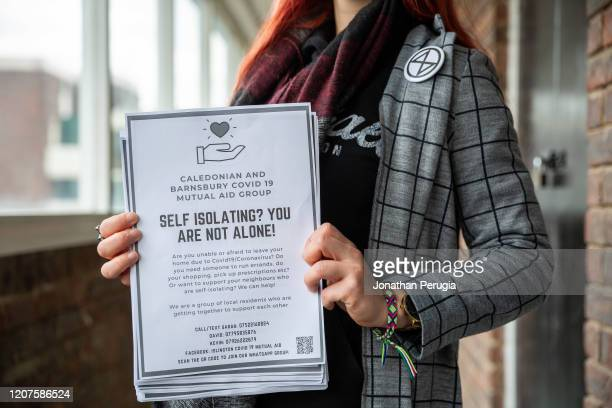 Volunteer Jessica Kleczka holding a leaflet for a local community support group called Mutual Aid on a housing estate near the Caledonian Road in...