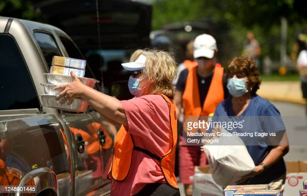 Volunteer Jodi Key loads food into a truck for a person there for the food distribution. At the Brandywine Heights Intermediate and Middle School in...