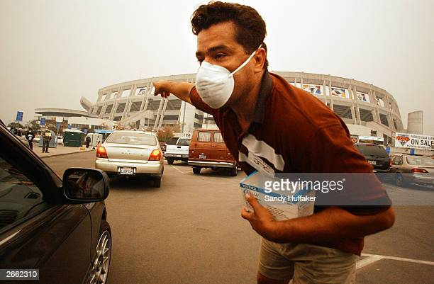 Volunteer Joe Enrique helps guide evacuees into the parking lot at Qualcomm Stadium October 27 2003 in San Diego California Evacuees from around San...
