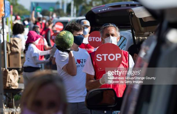 Volunteer Joseph Rice loads a watermelon during a drive-thru emergency food distribution in the parking lot of IKEA in Costa Mesa, CA on Thursday,...